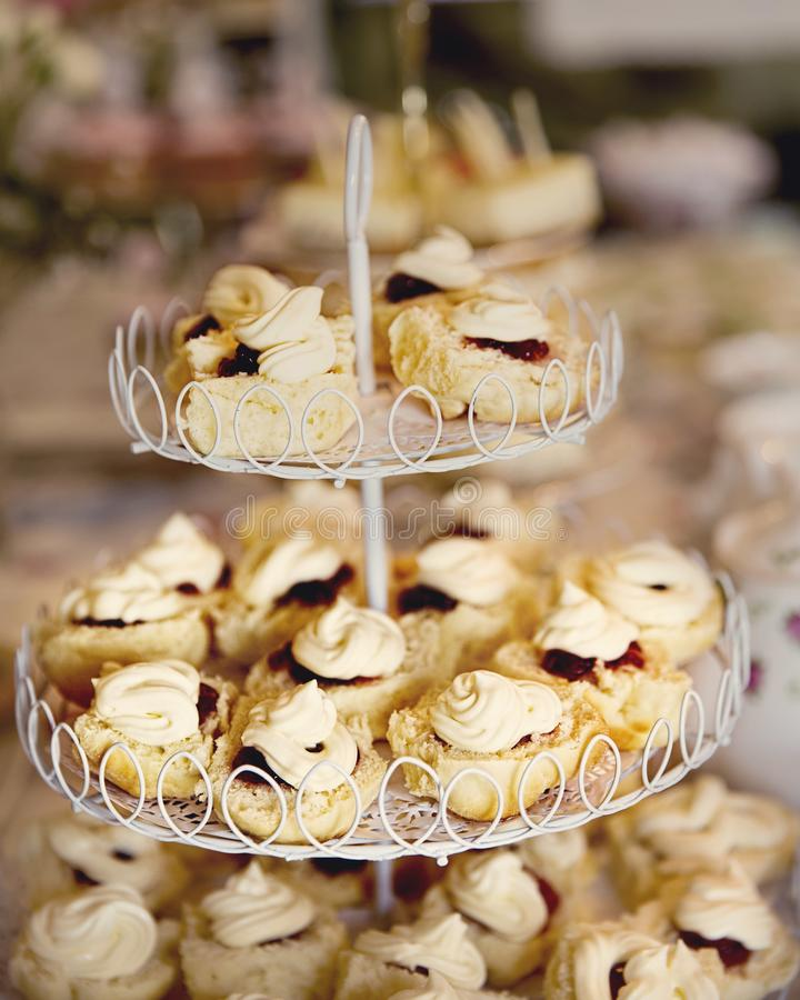 Scones With Jam And Cream. On a three tiered display stand. Ready for an elegant afternoon tea royalty free stock photo