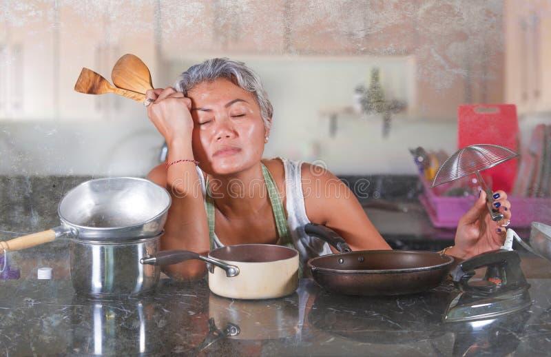 Scontento e stressante donna dai 40 ai 50 anni stanca e infelice in cucina a casa mentre fa lavori di casa e noia sensazione di c fotografie stock