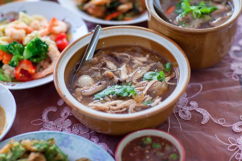 Scoop Chinese style soup; or braised fish maw in red gravy with eggs, mushroom,. And bamboo shoot in white bowl. Braised Fish Maw in Red Gravy with crab in bowl royalty free stock photo