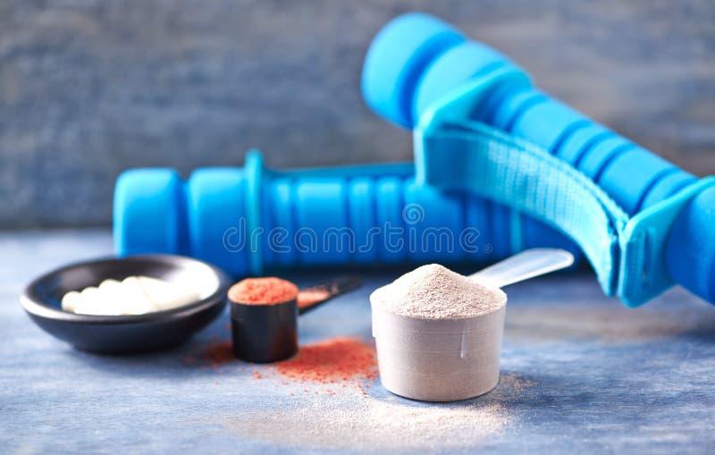 Scoop de protéine de lactalbumine, de capsules de poudre de créatine, de taurine et d'haltères bleues à l'arrière-plan Nutrition  images libres de droits