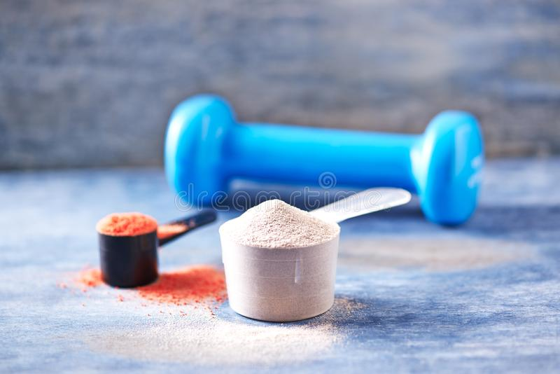 Scoop de protéine de lactalbumine, de poudre de créatine et d'une haltère bleue à l'arrière-plan Nutrition de sport photo libre de droits