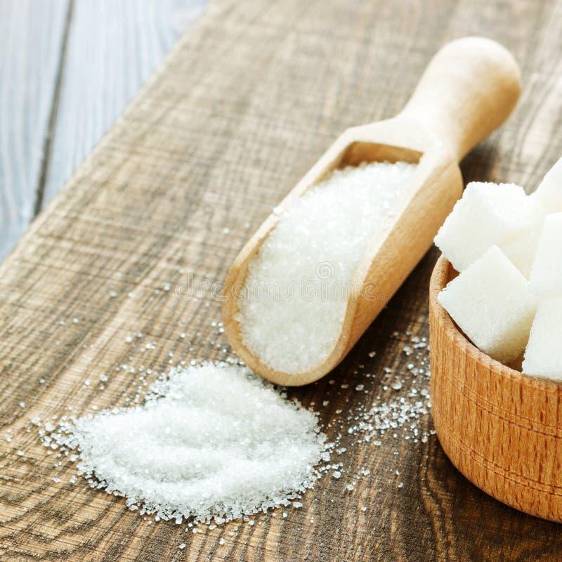 Scoop et cuvette en bois avec du sucre sur la table, plan rapproché photos stock