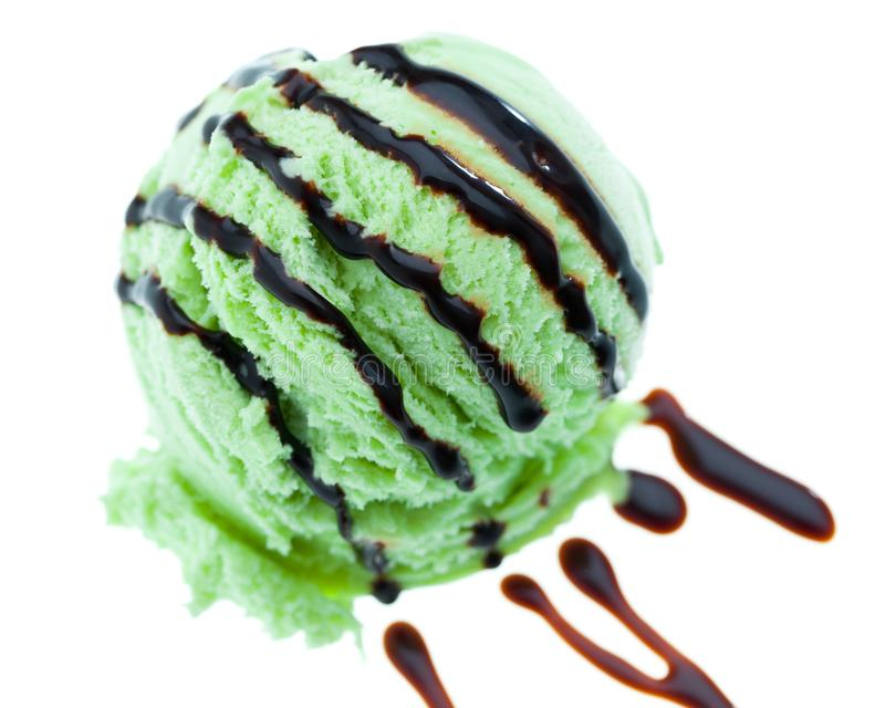 A scoop of mint ice cream topped with chocolate sauce isolated on white background royalty free stock photo