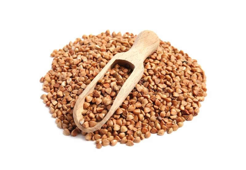Scoop and pile of uncooked buckwheat stock image