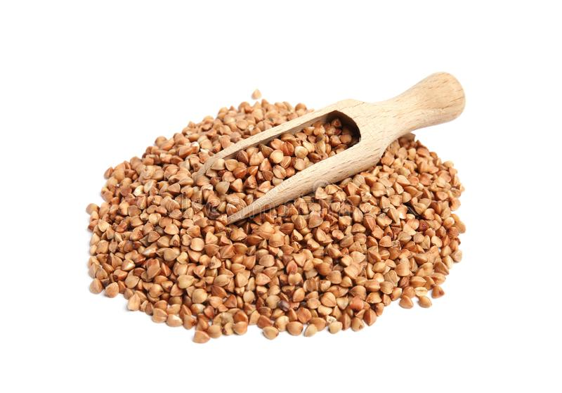 Scoop and pile of uncooked buckwheat royalty free stock photos