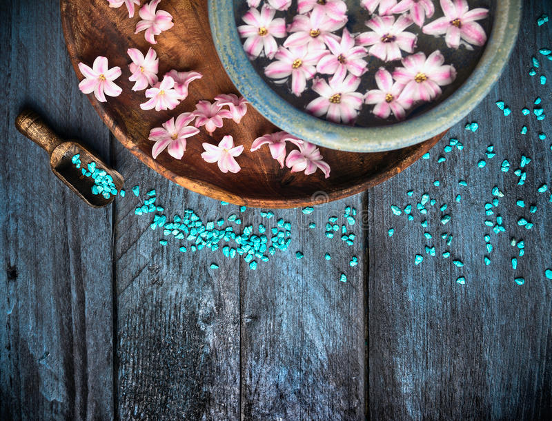 Scoop with sea salt bowl and flowers in water on blue wooden table, SPA background. Top view royalty free stock photo