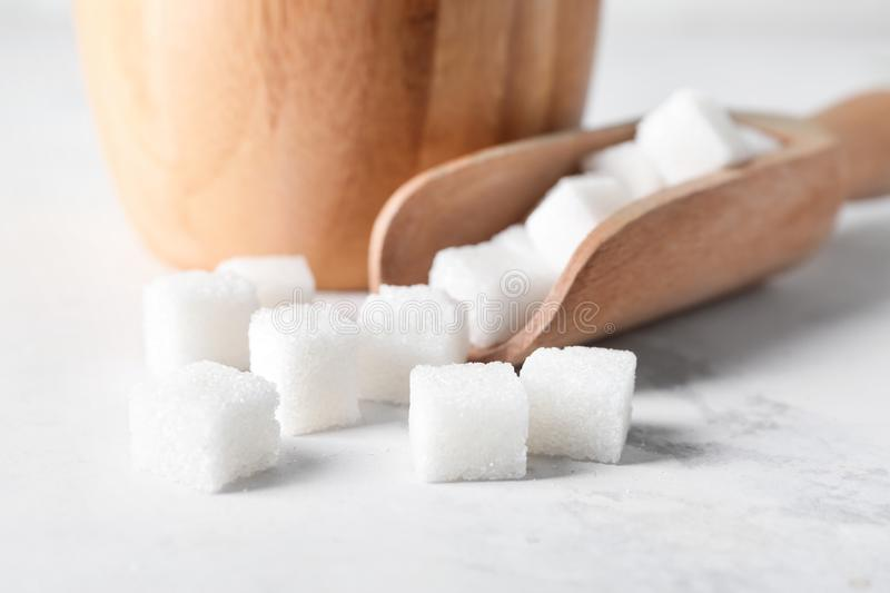 Scoop with sugar cubes on light table, closeup stock photography