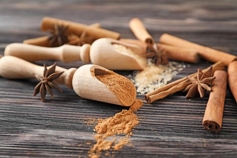Scoops with cinnamon powder and sugar on wooden background, closeup royalty free stock images