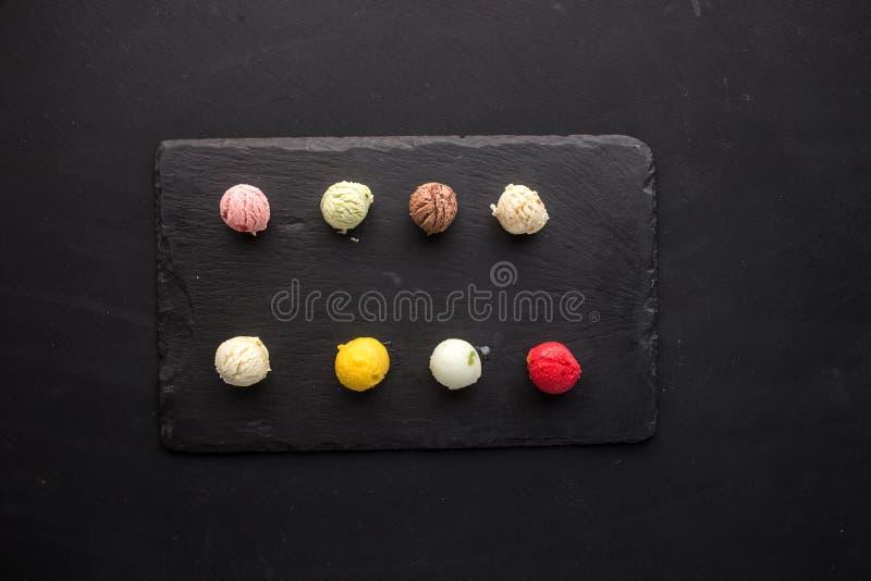 Scoops colorés de crème glacée avec différentes saveurs sur le conseil en pierre sur le fond noir photos stock