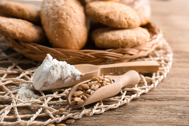 Scoops with flour and wheat grains on wooden table. Baking ingredients royalty free stock photos