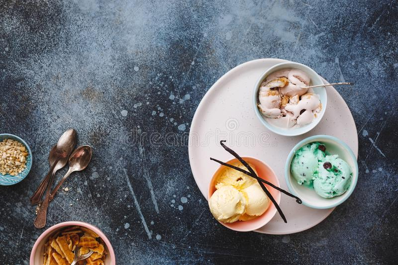 Scoops of mint, chocolate  and vanilla ice cream in different bowls stock photography