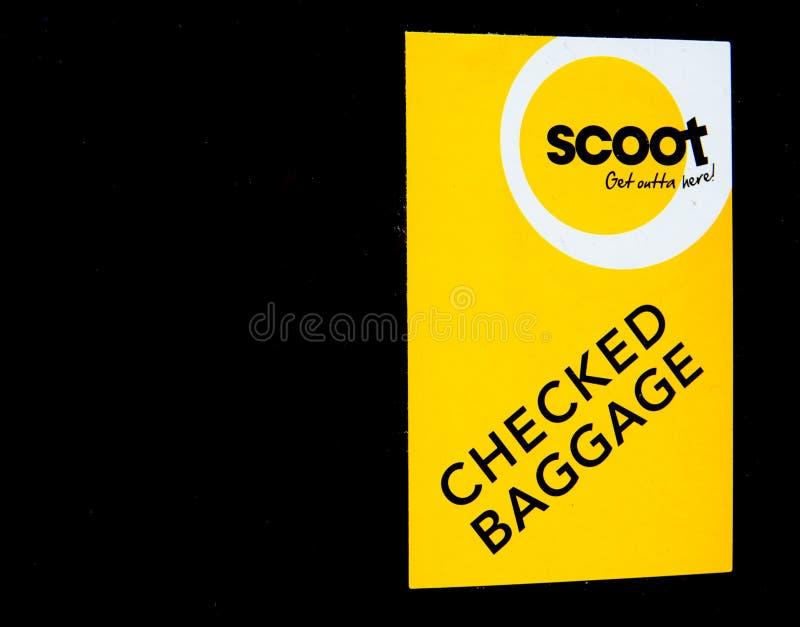 Scoot黄色贴纸`检查行李`附加到黑行李的航空公司 库存图片