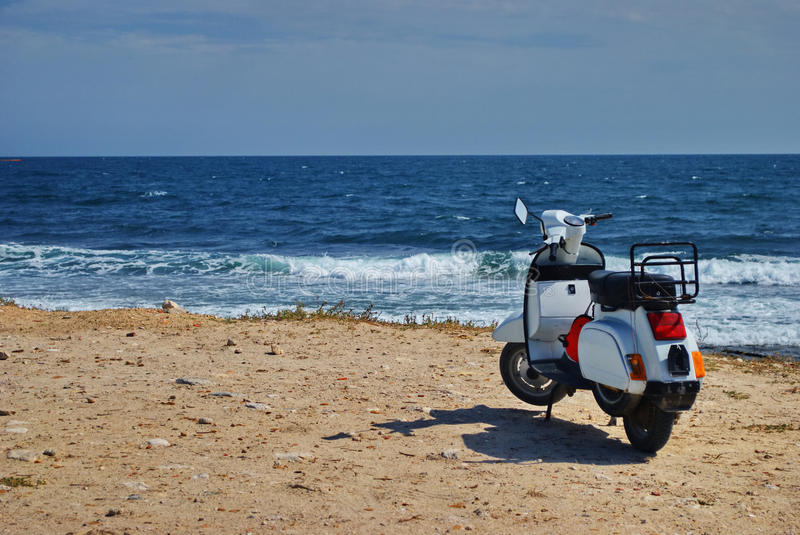 Scooter. White motor scooter with blue sea in background stock photo