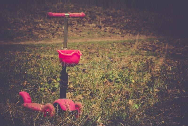 Scooter abstrait triste de seule solitude de concept de solitude en parc le jour d'été Élève du cours préparatoire montant un rou photographie stock