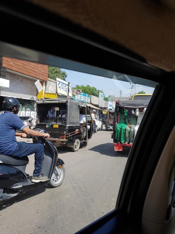 Scooter, autos carrying passengers and shops are seen in India. Road is full of traffic royalty free stock photography