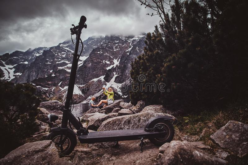 Scooter in the beautiful mountains with pine and low clouds. Beautiful mountains, low gloomy clouds, stones, pines and scooter at the front royalty free stock photos