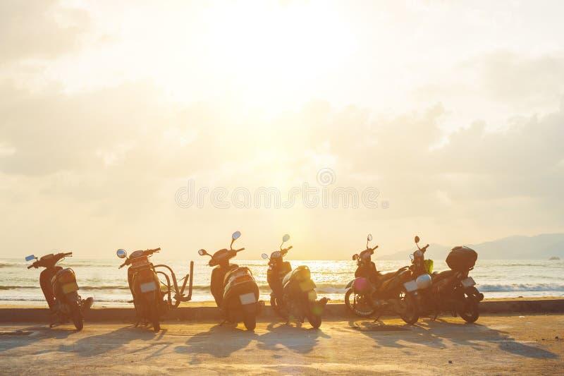 Scooter de silhouette au bord de la mer avec le fond de coucher du soleil photographie stock