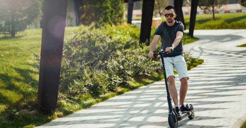 Scooter ?lectrique de coup-de-pied d'?quitation attrayante d'homme au beau paysage de parc photos stock
