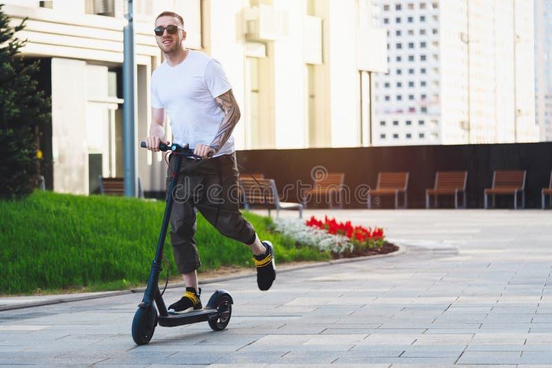 Scooter ?lectrique de coup-de-pied d'?quitation attrayante d'homme au fond de paysage urbain images libres de droits