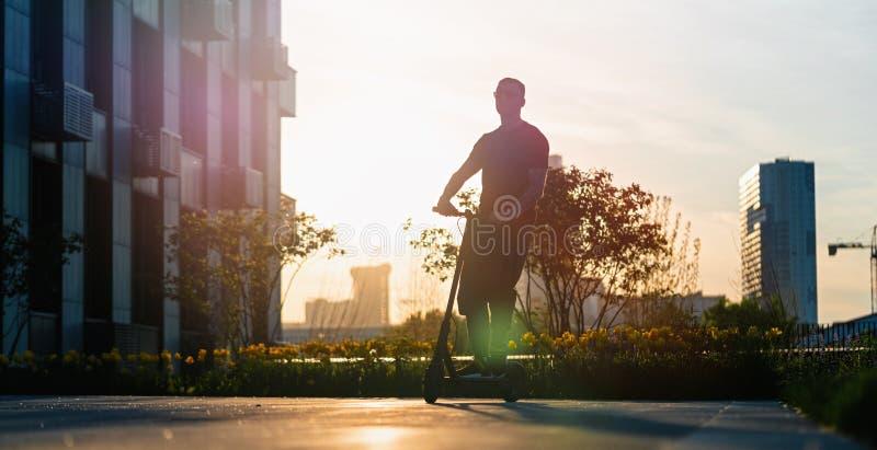 Scooter ?lectrique de coup-de-pied de noir d'?quitation d'homme au fond de paysage urbain au coucher du soleil image stock