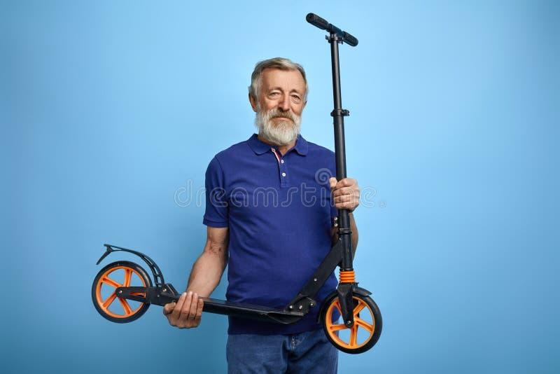 Scooter mûr beau de participation d'homme et regarder la caméra photos libres de droits