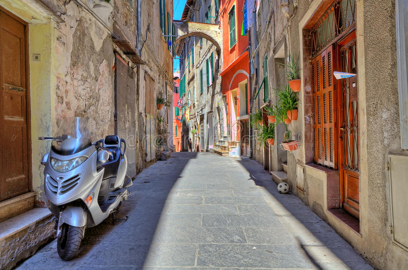 Scooter on narrow street in Ventimiglia, Italy. Scooter stands on narrow street among old residential houses in Ventimiglia, Italy royalty free stock images