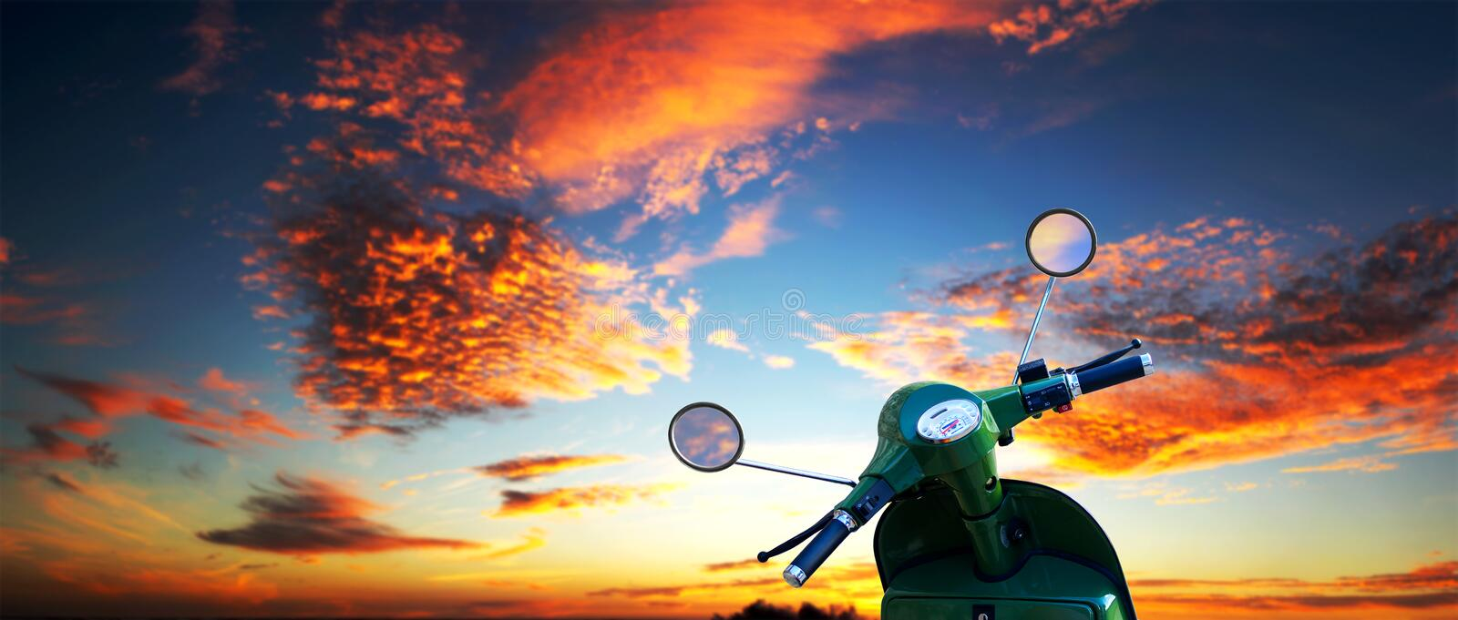 Scooter over a dramatic sky. Scooter over a beautiful vibrant sunset sky - Detailed clipping paths for both motorcycle body and mirrors royalty free stock photo