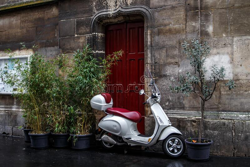 The scooter parked near red door.  stock photo