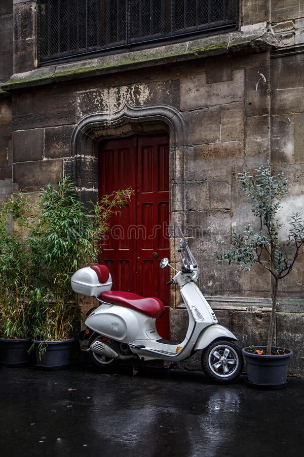 The scooter parked near red door.  royalty free stock photography