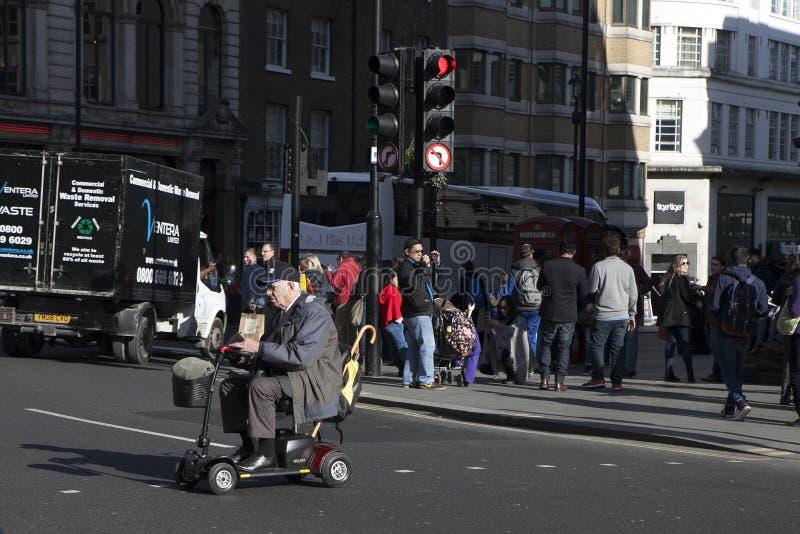 Scooter plus âgé de mobilité d'entraînement d'homme par la rue de Londres photos libres de droits