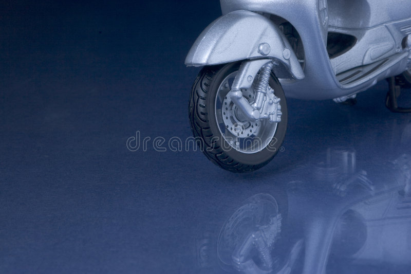 Scooter reflexion. Toy vespa scooter hovering over a blue reflecting surface stock image