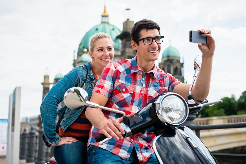 Scooter riding tourists taking selfie in front of Berlin Cathedr stock photo