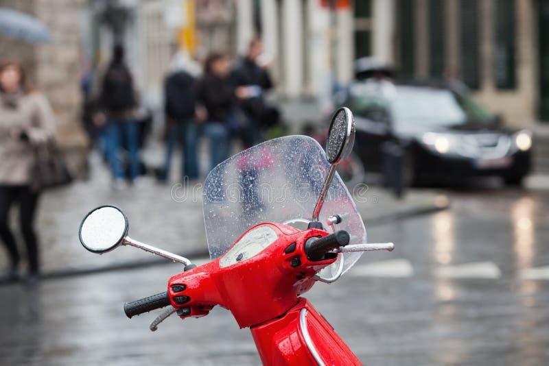 Scooter rouge devant une scène de circulation photographie stock libre de droits