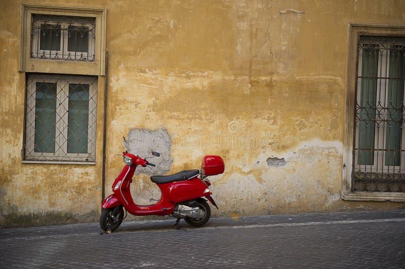 Scooter rouge lumineux de Vespa dans une rue urbaine image libre de droits