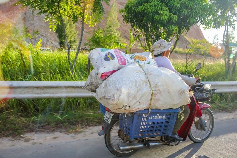 Scooter thaïlandais portant les sacs géants photos stock