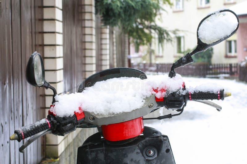 Scooter unter dem Schnee auf der Straße von Krakau, Polen lizenzfreie stockfotos