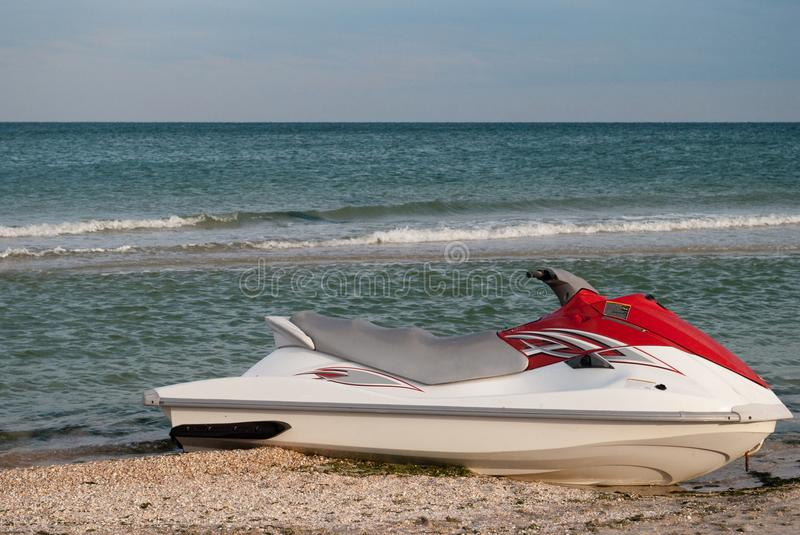 Scooter white water jet with red on the seashore. seashore, beach, blue sky. Water scooter white water jet with red moored on the seashore, summer day, against royalty free stock photos