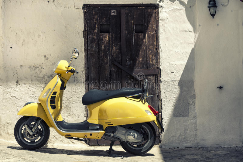 Scooter yellow motorcycle in front of old houses with white wall royalty free stock photo