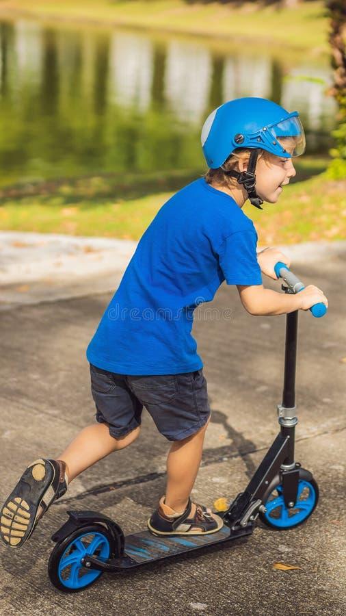 Scooters de monte de garçon, extérieurs en parc, été Les enfants sont heureux jouant dehors le FORMAT VERTICAL pour Instagram photos stock