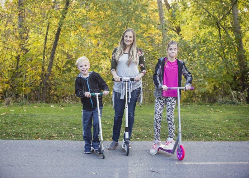 Scooters heureux d'équitation de famille ensemble sur une voie pavée dehors image libre de droits
