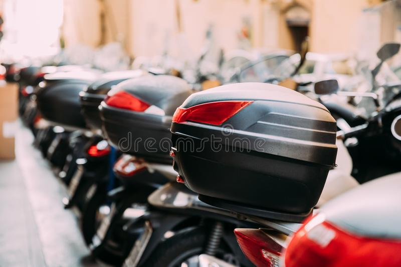 Scooters With Removable Trunks. Many Motorbikes, Motorcycles, Scooters Parked In Row In City Street. Trunk Or Top-box Is royalty free stock photography