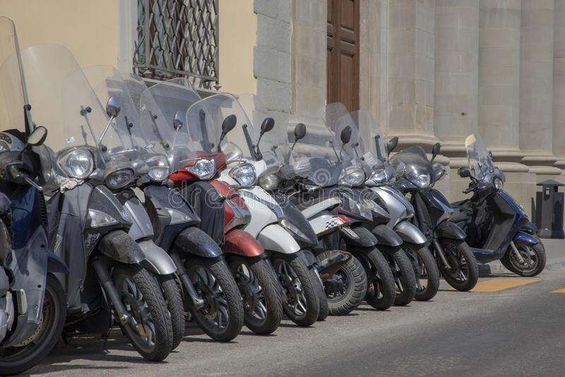 Scooters in a row stock images
