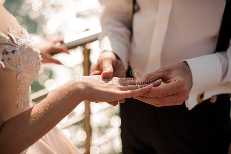 Scopa che mette una fede nuziale dorata ad un dito tenero della sposa immagine stock