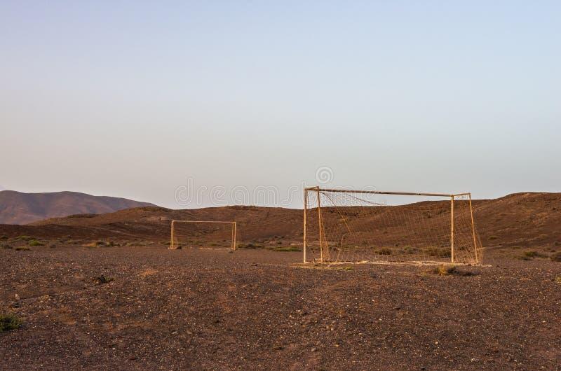 Scopo abbandonato di calcio nel deserto al tramonto immagini stock