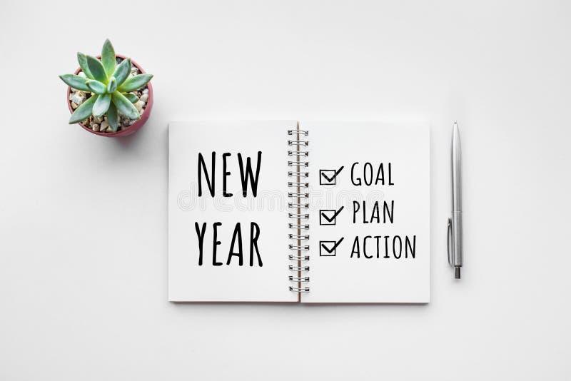 Scopo del nuovo anno, piano, testo di azione sul blocco note con gli accessori dell'ufficio fotografia stock libera da diritti