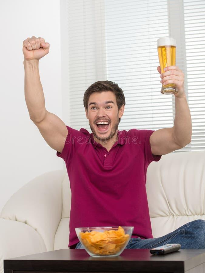 Scopo! Giovani felici che tengono un vetro di birra nella suoi mano e expre fotografia stock libera da diritti