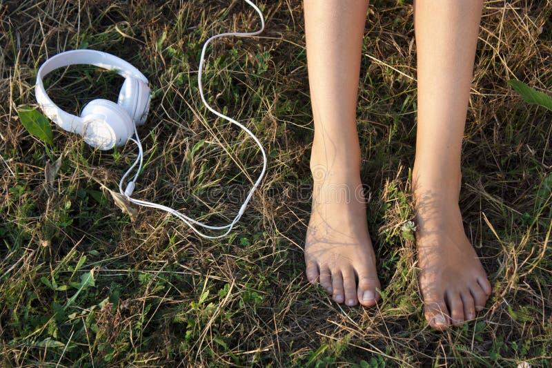 Scopra i piedi femminili su un'erba e sulle cuffie fotografia stock libera da diritti