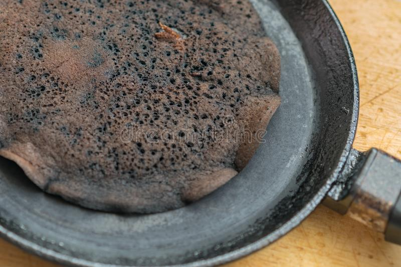 Scorched pancake closeup in a frying pan stock photography