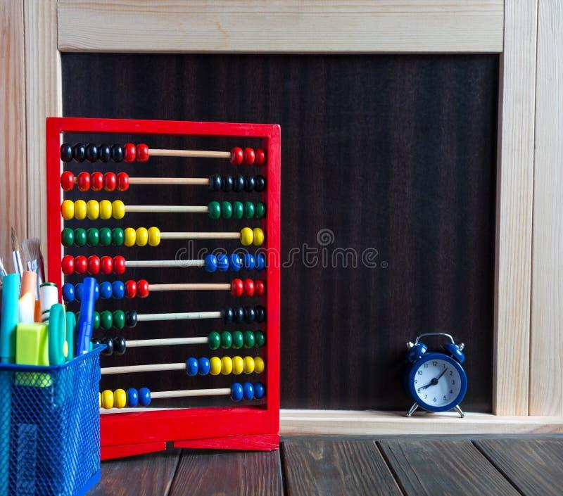 Scores, klok en kantoorbehoeften op de houten lijst dichtbij bord Studieconcept stock foto's