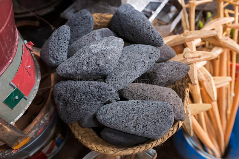 Scoria stone, volcanic rock, black lava rough stones full of holes vesicles in dark color selling at Mto wa Mbu village, Tanzania royalty free stock images